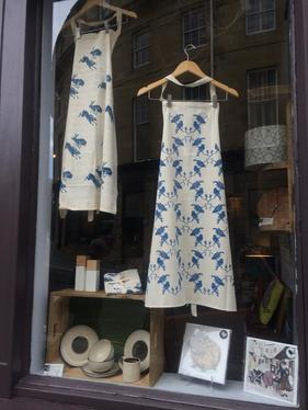Photo of Posit & Whatsis Shopfront displaying 'Chatterbox Apron and Tea towel designed by Gloria Dean.